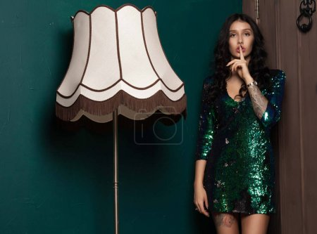 Photo for Portrait of an attractive fashionable young brunette woman in green dress. - Royalty Free Image
