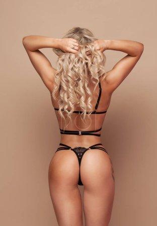 Photo for Sensual blonde beautiful woman posing in elegant black lingerie, looking at camera. Beige background. Studio shot. - Royalty Free Image