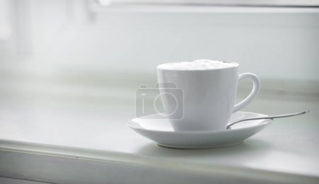Photo for White cup of hot coffee served on window - Royalty Free Image