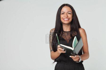 Photo pour Portrait d'une jeune femme avec longs cheveux noirs portant une robe noire et tenant un planificateur et un stylo. Fond de mur gris - image libre de droit