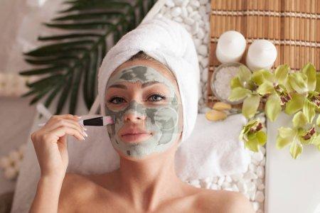 Photo for Spa teen girl applying facial clay mask. Beauty treatments. - Royalty Free Image