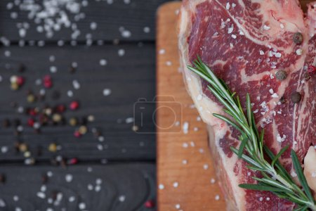 Photo for Raw meat steak on dark wooden background ready to roasting - Royalty Free Image