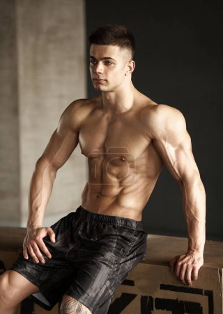 Photo for Healthy young man standing strong in the gym and flexing muscles - muscular athletic bodybuilder fitness model posing after exercises - Royalty Free Image