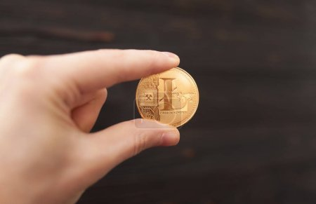 Photo for Hand is holding gold litecoin on a brown background. Business value litecoin are expensive. - Royalty Free Image