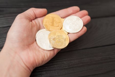 Photo for Bitcoins, litecoin and ethereum in hand on old wooden background - Royalty Free Image