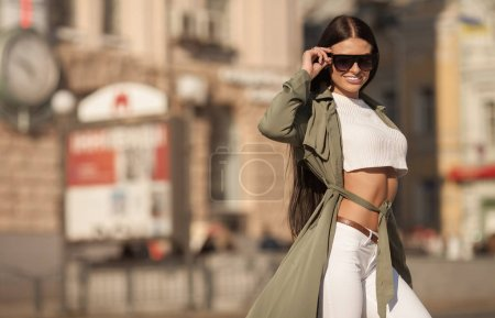 Photo for Portrait of happy smiling woman standing on the square on sunny summer or spring day outside, cute smiling woman looking at you, attractive young girl enjoying summer, filtered image, flare sunshine - Royalty Free Image