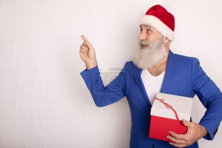 Photo for Holly jolly xmas, new year is soon! Be ready, prepare. Sales, discounts, presents, gifts selling time. Man wearing blue suit and red hat. - Royalty Free Image