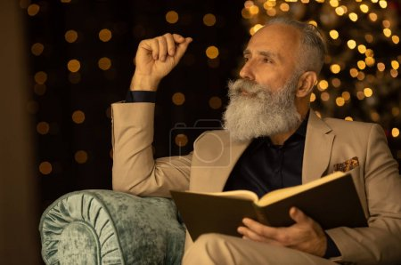 Photo pour Involved in reading. Bearded  businessman sitting in armchair feeling involved in reading - image libre de droit