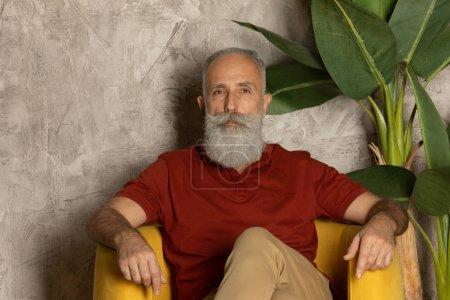 Photo pour Bearded senior man  relaxing in yellow armchair. - image libre de droit