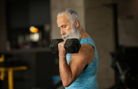 Photo for Senior man in sports clothing in gym working out with weights. - Royalty Free Image