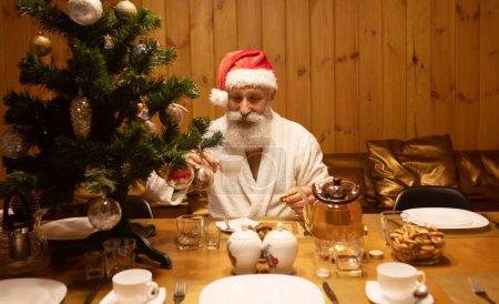 Photo for Senior man Santa claus drinking tea. New year celebration. - Royalty Free Image