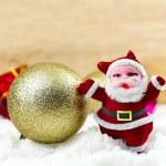 Постер, плакат: Small Santa Claus and gold snow ball on white snow and wooden ba