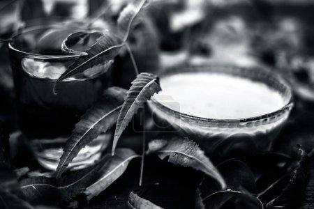 Photo pour Remède capillaire aux herbes médicinales ayurvédiques polyvalentes Neem ou Nim ou lilas indien dans un bol en verre avec des feuilles de neem et de l'eau douce pour les pellicules ou les problèmes de démangeaisons de la peau des cheveux. Plan horizontal . - image libre de droit