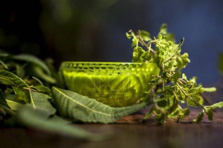 Photo pour Gros plan du bol en verre rempli de tulsi ou de basilic et de neem ou de pâte de lilas indien avec du neem frais et des feuilles de tulsi sur une surface en bois brun . - image libre de droit