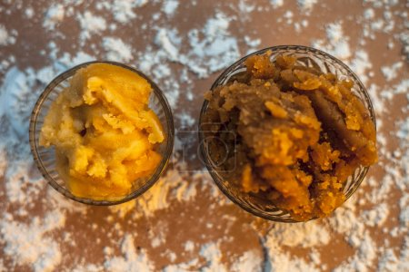 Photo for Close up of Indian Gujarati popular dish Atte ka sheera or Halwa-Karah parshad in a glass bowl on a brown surface with some spread wheat flour and some jaggery in a glass bowl. Horizontal top shot. - Royalty Free Image