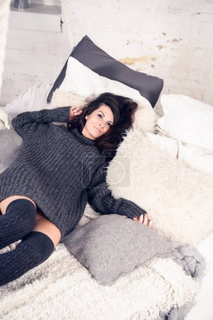 Beautiful woman in bed wearing sweater and knitted socks
