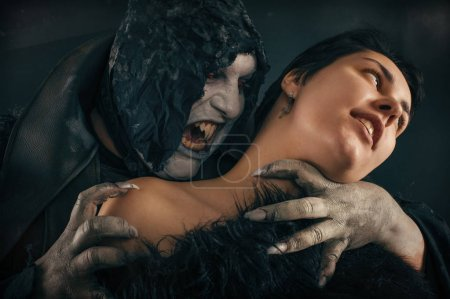 Scary vampire devil biting young woman. Medieval gothic nightmar