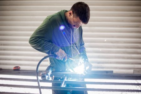 Industrial worker welding the steel structure in the workshop