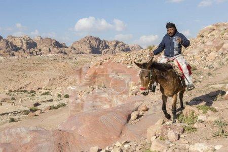 Photo for Petra, Jordan December 24th, 2015: Bedouin man riding a horse in the ancient Nabatean city of Petra, Jordan - Royalty Free Image