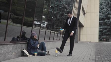 Photo pour L'homme d'affaires bannit le sans-abri barbu et renvoie sa tasse avec des pièces . - image libre de droit
