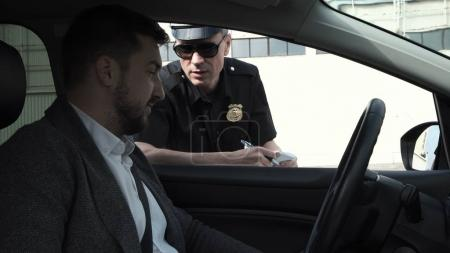 Photo for Policeman stopping a driver in a car to question him through the window on a traffic offence - Royalty Free Image