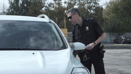 Photo pour Un policier arrête le conducteur d'un véhicule et l'interroge sur une infraction présumée par la fenêtre ouverte de la voiture - image libre de droit