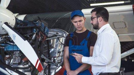 Photo pour Mécanicien se tenant près d'avion, de chercher à moteur et de parler avec Rapporteur pour avis. - image libre de droit