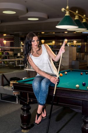Photo for Beautiful brunette sitting on billiard table with cue - Royalty Free Image