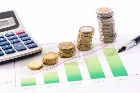 Photo pour Graphique d'affaires, pièce en euros, calculatrice et stylo isolés - image libre de droit