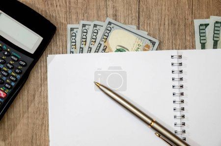 Calculator, us dollar, notebook with pen on desk