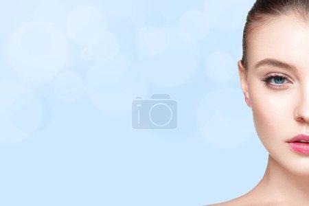 Photo pour Portrait de demi visage de femme avec frais clair nude maquillage et peau saine sur fond bleu, concept de soins de la peau - image libre de droit