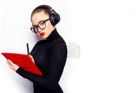 Woman in black with headphones and red lips posing with red board on white background