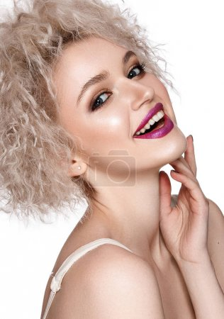 Smiling young model with curly hairstyle and pink lipstick posing on white background