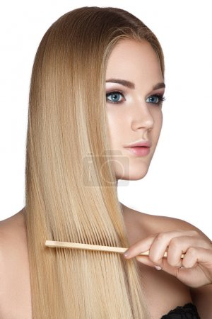 Portrait of blonde woman with comb on white background