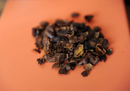 The dried flesh of the coffee berries cascara is scattered on the orange surface, close-up