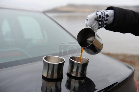 Girl in mittens pours coffee from the pitcher on the cups on the car trunk. Uninhabited monochrome landscape