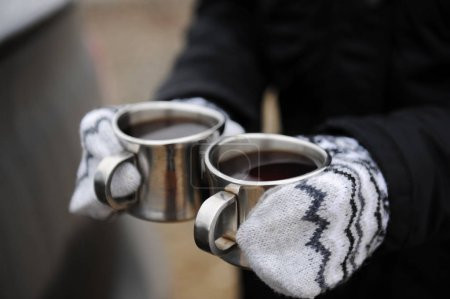 Two metal cups with coffee in hands in mittens close-up on car background. Brewing coffee in the open air