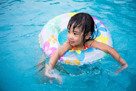 Photo for Happy Asian Chinese Little Girls Swimming In The Outdoor Pool - Royalty Free Image