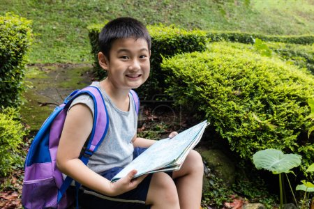 Smiling Asian Chinese boy holding map sitting in the forest