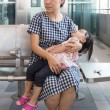 Asian Chinese mother carrying sleeping daughter in...