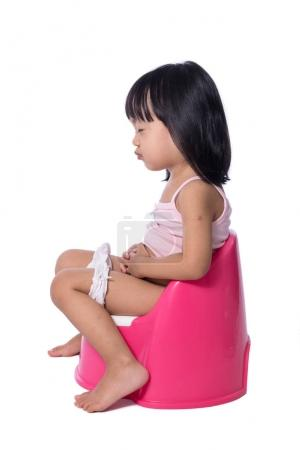 Asian chinese little girl sitting on chamberpot