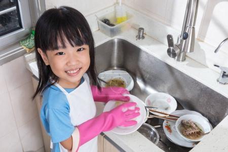Photo pour Asiatique chinois petite fille laver la vaisselle dans la cuisine à la maison - image libre de droit