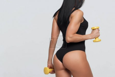 Fitness woman exercising crossfit holding dumbbell...