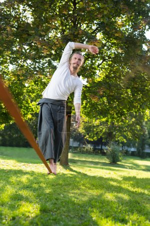Photo for Slacklining is a practice in balance that typically uses nylon or polyester webbing tensioned between two anchor points - Royalty Free Image
