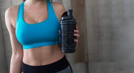 Fitness woman with whey shaker