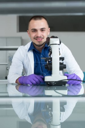 Scientist with microscope in a laboratory