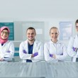 Постер, плакат: Young scientists in white uniform working in laboratory