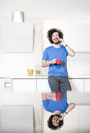 Man in kitchen using cell phone