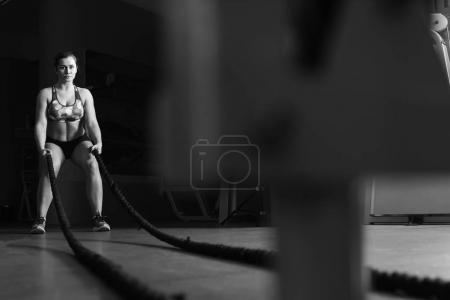 Photo for Fitness woman work out with Crossfit battling ropes at gym. - Royalty Free Image