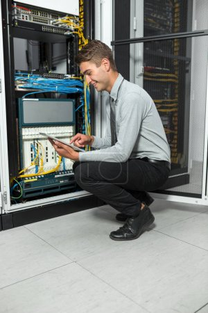 Young man is standing next to the racks with computer equipment